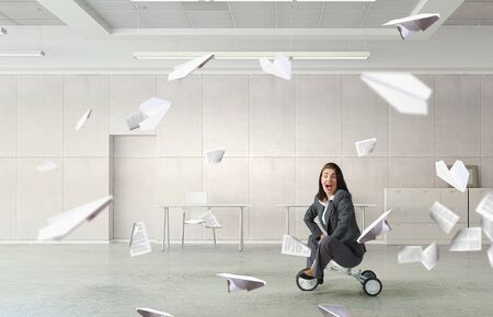 wheeled: Young pretty businesswoman riding three wheeled bike in office