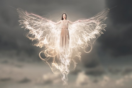 Beautiful woman in long dress with wings in gray sky