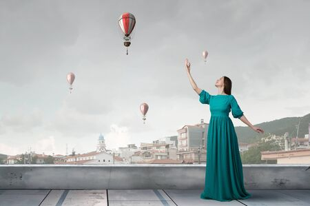 Donna elegante in abito lungo verde sulla cima dell'edificio