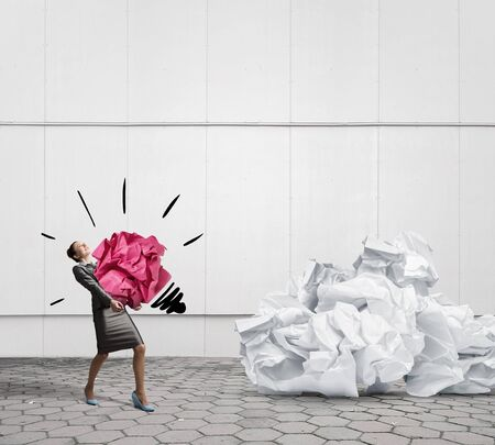 hard to find: Woman carrying with effort big crumpled ball of paper as creativity sign