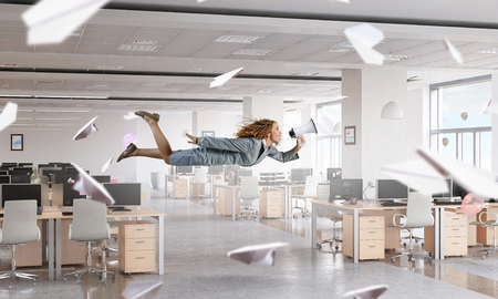 careless: Young careless businesswoman flying in modern office interior