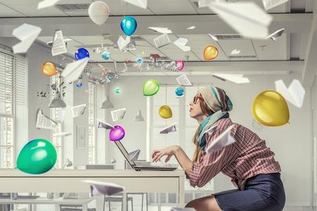 Jonge hipster meisje zitten aan tafel en werken op de laptop Stockfoto