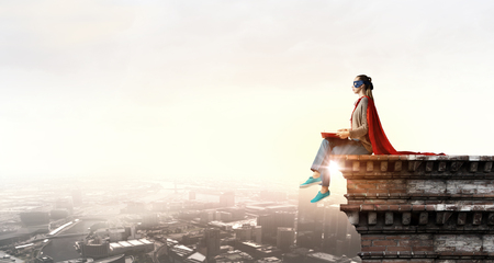 Young thoughtful woman in red cape and mask on building roof read book