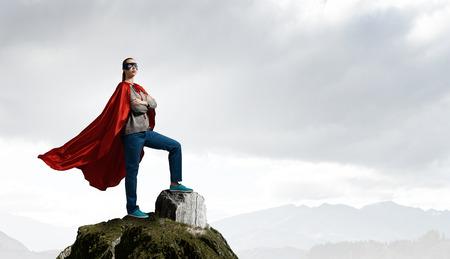 Jonge zelfverzekerde vrouw in rode cape en masker op rock top