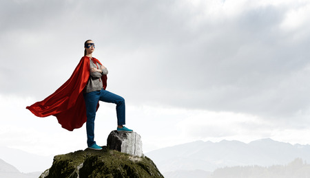 Young confident woman in red cape and mask on rock top