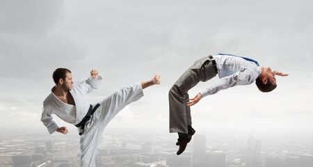 human relations: Young determined karate man fighting with businessman in suit Stock Photo