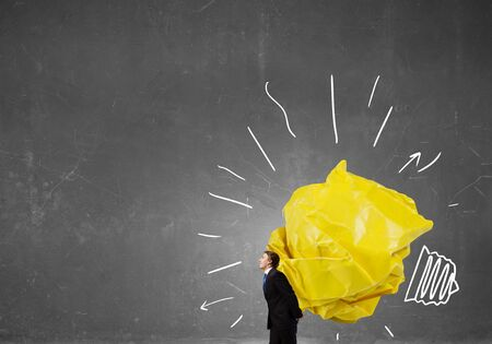 hard to find: Businessman carrying with effort big crumpled ball of paper as creativity sign Stock Photo