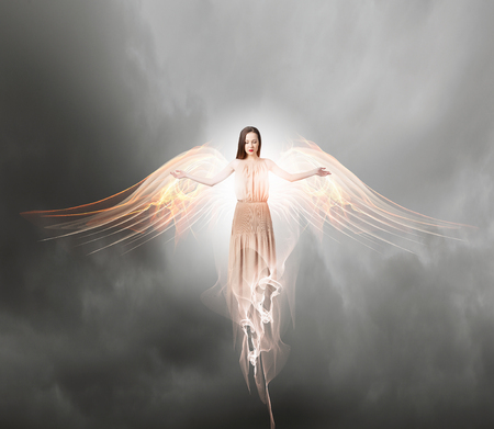 dark: Beautiful woman in long dress with wings in gray sky