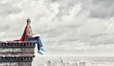 Jonge doordachte vrouw in rode cape en masker op het bouwen van daklezenboek