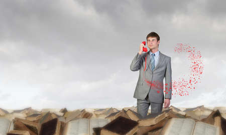 important phone call: Handsome businessman talking on red phone handset Stock Photo