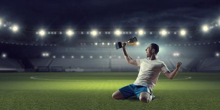승리 컵을 들고 승리를 축하하는 축구 선수