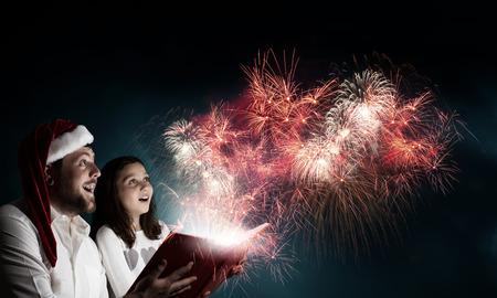pere noel: Jeune père et la fille de lire livre et la lumière provenant de pages