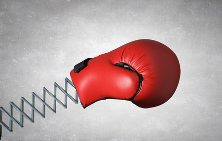 Red boxing glove on spring on concrete background