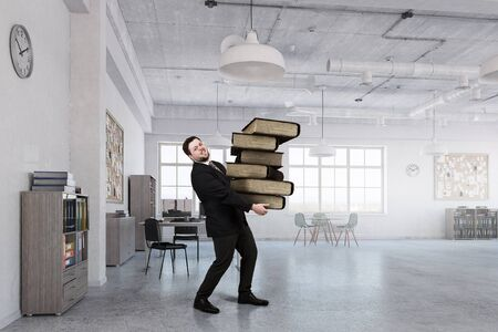 pile books: Young businessman in modern office carrying pile of books