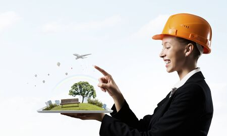 hat project: Woman engineer in hard hat showing construction project Stock Photo