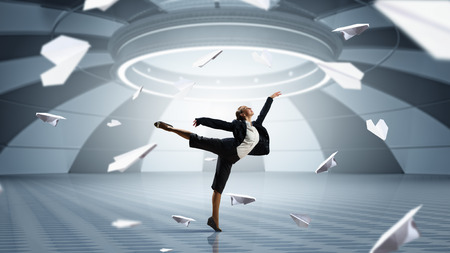 futuristic interior: Young dancing businesswoman in suit in futuristic interior