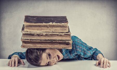 suppressed: Student girl pressed with pile of books to table