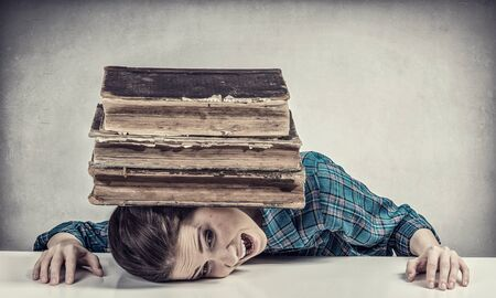 Student girl pressed with pile of books to table