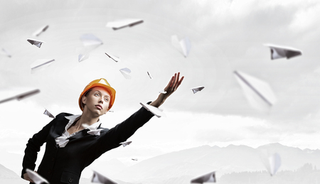 reaching hand: Young engineer woman reaching hand and paper airplanes flying around