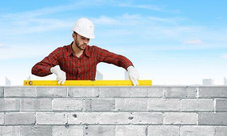 journeyman: Builder man in checked shirt using measuring level