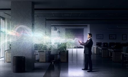 dark interior: Adult businessman in office dark interior using tablet pc