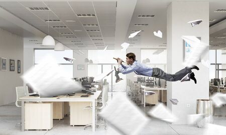 fife: Young businessman flying in office and playing fife