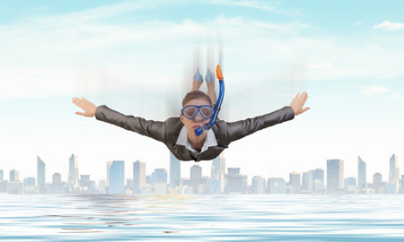 sky diving: Young businesswoman in suit and diving mask flying in sky