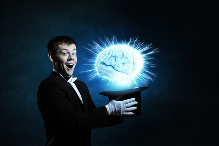 feeling happy: Young cheerful businessman making tricks with magic hat