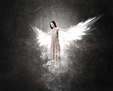 Hermosa mujer en vestido largo con alas en el fondo de concreto