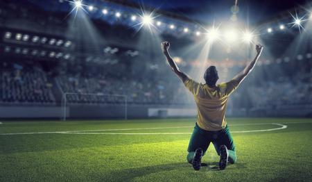Jogador de futebol que comemora a vitória, mantendo vitória copo Imagens