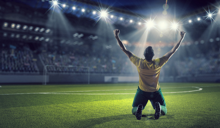 Soccer player celebrating victory while holding win cup Stock Photo