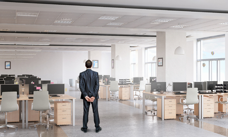 Thoughtful businessman standing with back in empty office Foto de archivo