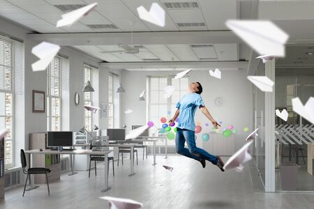 careless: Young careless man flying in modern office interior Stock Photo