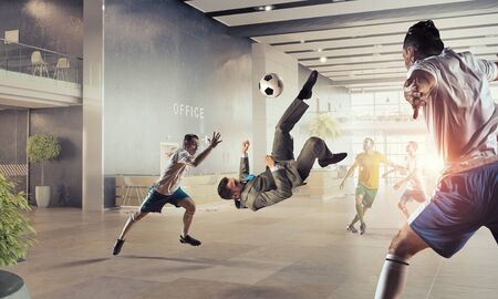 fun at work: Players and businessman playing soccer ball in modern office