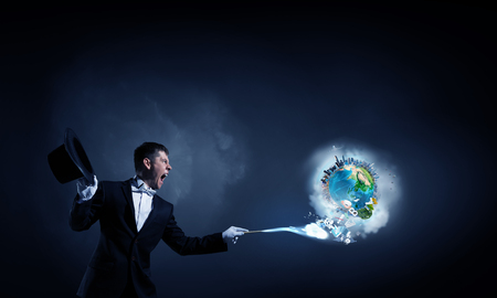 feeling happy: Young cheerful businessman making tricks with magic hat. Elements of this image are furnished by NASA Stock Photo