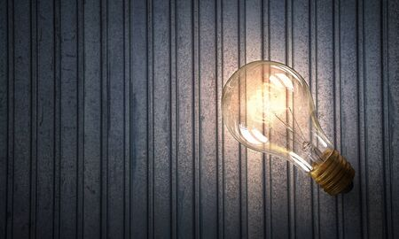 metal filament: Power and energy concept with glass glowing light bulb o backdrop