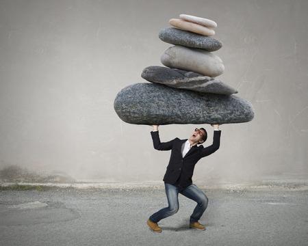 Jonge sterke man met grote steen boven het hoofd
