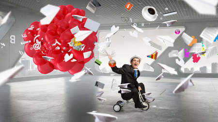 wheeled: Young funny businessman riding three wheeled bicycle in office Stock Photo