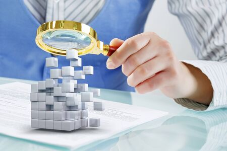 analyze: Hands of woman looking in magnifier at 3d illustration cube figure