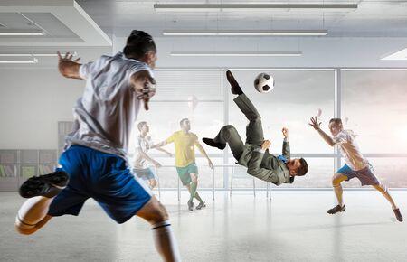 Los jugadores y los negocios que juega el balón de fútbol en la oficina moderna