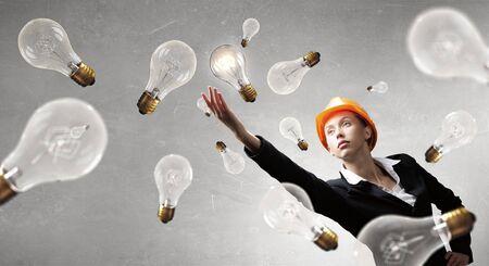 reaching hand: Young engineer woman reaching hand and glass bulbs around