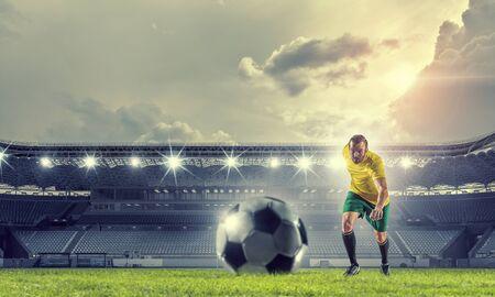 Determined football player at stadium hitting ball Foto de archivo