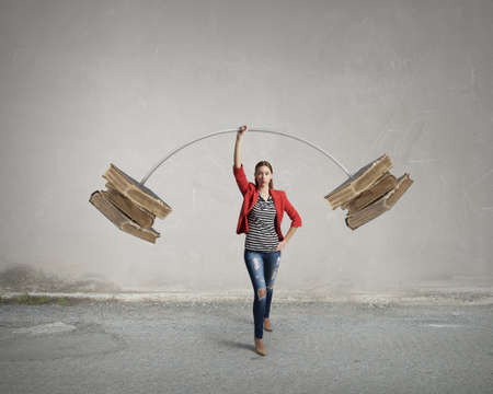 above head: Young woman student in red jacket lifting barbell above head