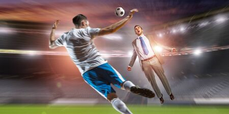 green office: Young businessman in suit playing football at stadium Stock Photo