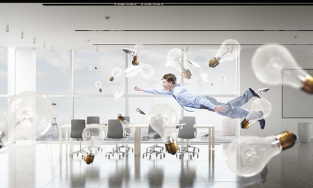 careless: Young careless businessman flying in modern office interior