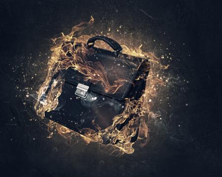 black briefcase: Black briefcase in fire flames on dark background