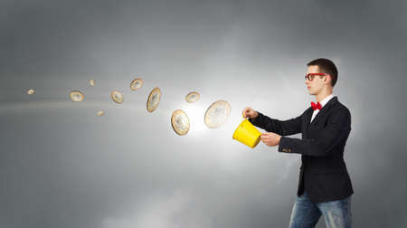 bucket of money: Young funny man in glasses with yellow bucket in hands