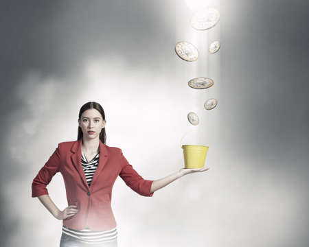 bucket of money: Young woman in red jacket holding yellow bucket in hands