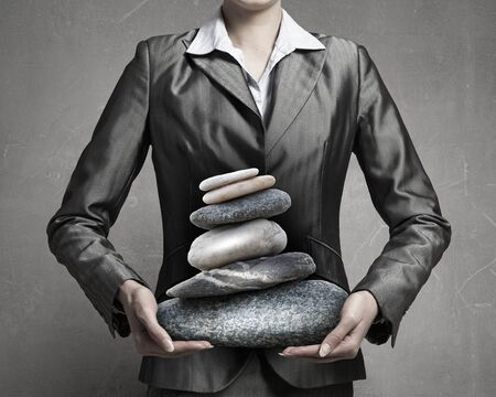 oppressed: Close view of businesswoman holding stack of stones in hands Stock Photo