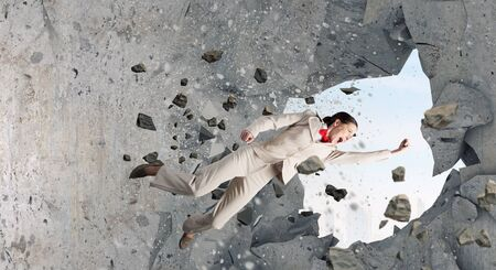 fedup: Emotional businesswoman breaking stone wall with karate punch